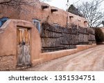 Adobe House With Rustic Wooden...