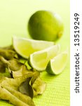 Small photo of Lime with kafir leaves on the green table (shallow dof)