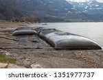Small photo of Walenstadt, Switzerland - 27.03.2019: GeoTube sludge dewatering containers are seen setup on the beach of the Walensee in Walenstadt to store sludge removed from the Walenstadt marina.