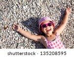 little girl lying on a pebble... | Shutterstock . vector #135208595