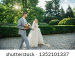 bride and groom walking on the... | Shutterstock . vector #1352101337