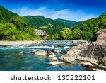 shore of a mountain river with stones and iron bridge - stock photo