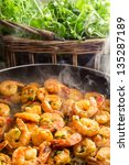 Hot shrimp fried in a pan with fresh herbs - stock photo