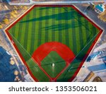 Aerial wide angle view of a green baseball field diamond in the morning sunlight.