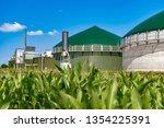 biogas plant behind maize field | Shutterstock . vector #1354225391