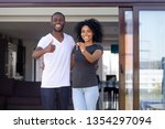 Small photo of Overjoyed african married couple standing on summer terrace porch near new modern house. Happy wife hold keys embracing beloved husband showing thumbs up sign. Property ownership, loan tenancy concept