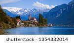Panoramic view on the Brienz town on lake Brienz by Interlaken, Switzerland. Old fishing town with beautiful church and snow covered blue Alps mountains on background. Switzerland, Bohemia, Europe. - stock photo