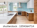 Stock photo beautiful kitchen in contemporary luxury home with waterfall island counter to ceiling backsplash 1354364714