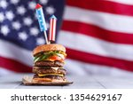 Small photo of a big burger with three juicy beef patties bonded with American flag firework skewers. burgar concept for the day of independence day celebration of fourth of july