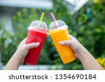 fruit smoothie. hand holding... | Shutterstock . vector #1354690184