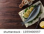 Stock photo herring on paper with lemon slices onion rings parsley dill salted herring on a brown rustic 1355400557