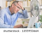 Small photo of Man suffers from heat while working in the office and tries to cool off by the fan
