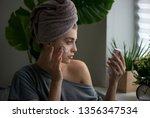 young woman applying face cream ... | Shutterstock . vector #1356347534