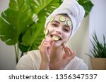 young woman applying face mask... | Shutterstock . vector #1356347537