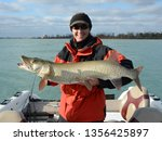 A spotted silver and olive green muskie fish being held horizonally by a woman in a red and black jacket and hat on a sunny day on the Detroit River at Lake St Clair
