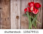 Red Tulips On An Antique Woode...