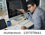 Serious Indian programmer in eyeglasses pointing at computer monitor and checking the statistics of website in document while working at office - stock photo