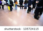 People waiting for their bags at airport conveyor belt - stock photo