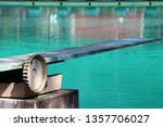 Small photo of Springboard at the swimming pool. It is a strong, flexible board from which someone can jump in order to gain added impetus when performing a dive.