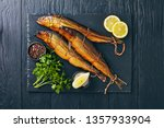 Stock photo hot smoked herrings on a black slate tray with lemon slices parsley and peppercorns view from 1357933904