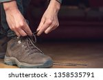 man puts his brow leather boots ... | Shutterstock . vector #1358535791