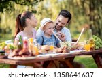 family having a barbecue in the ... | Shutterstock . vector #1358641637