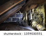 Crawl space under the eves of a house showing old fibreglass insulation, pipework, rafters, breezeblock construction and old boarding.