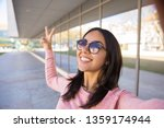 smiling woman showing victory... | Shutterstock . vector #1359174944