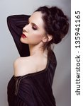 Small photo of Beautiful woman with brown hair braided in upstyle wearing black off shoulder dress on studio background