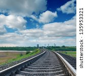 railroad to horizon under clouds - stock photo