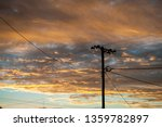 Silhouette Of Power Pole And...