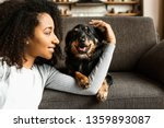Stock photo beautiful african american woman with cute dog at home 1359893087
