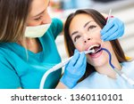 dentist curing oral cavity at... | Shutterstock . vector #1360110101