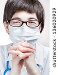 Beautiful female doctor wearing glasses and a mask close-up, hands near face - stock photo