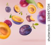 Stock photo flying in air fresh ripe whole and cut plums with leavs isolated on pastel pink background high 1360847234
