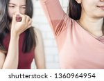 Small photo of Asian woman having problem sweat under armpit with friend smelling stink in background