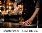 Stock photo bartender pouring an alcohol from the measuring glass cup through the strainer to the cocktail on 1361183957