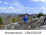 An older man taking a break from hiking to enjoy the view at an overlook in the mountains. - stock photo