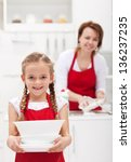 Little girtl helping mother to do the dishes carrying the plates - stock photo