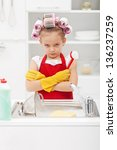 Grumpy little girl washing dishes in the kitchen - closeup - stock photo