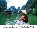 A woman in a river boat in Ninh Binh.  Mountains of northern Vietnam.