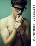 Emotive portrait of a beautiful (handsome) muscular male model with nice body in trendy glasses posing over green background. Vogue style. Perfect skin and body. Studio shot. - stock photo