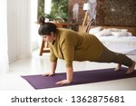 Small photo of Health, fitness and sports concept. Plus size young brunette woman doing plank exercise on mat in cozy bedroom interior, going to loose extra pounds, become strong and fit, training endurance