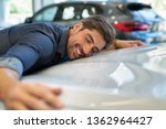 Small photo of Happy young man hugging his new car in showroom. Satisfied guy with closed eyes embracing the hood of the automobile. Dreaming man lying on car bonnet hugging it.