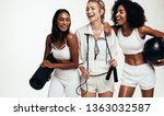 Small photo of Cheerful young multi-ethnic female friends taking break after workout session. Diverse group females in sportswear with yoga mat, skipping rope and medicine ball against white background.