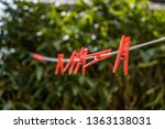 Red plastic clothes pegs on a...