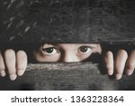 Stock photo bored little girl frightened child is spying through a wooden fence scared child girl human 1363228364