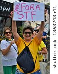 """Small photo of Sao Jose dos Campos / Sao Paulo / Brasil - April 7, 2019: At the demonstration a woman with the plaque """"Fora STF"""" in repudiation to the Federal Supreme Court"""