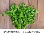 Small photo of Fresh raw cilantro bunch in metal bucket on wooden background. Organic cilantro closeup in rustic style, vegetarian food. Flat lay Parsley indispensable source of vitamins A, C, K, B1, B2, PP, E, C