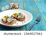 Stock photo smorrebrod sandwiches with herring boiling egg chopped green onions on white plate on wooden table 1364017361